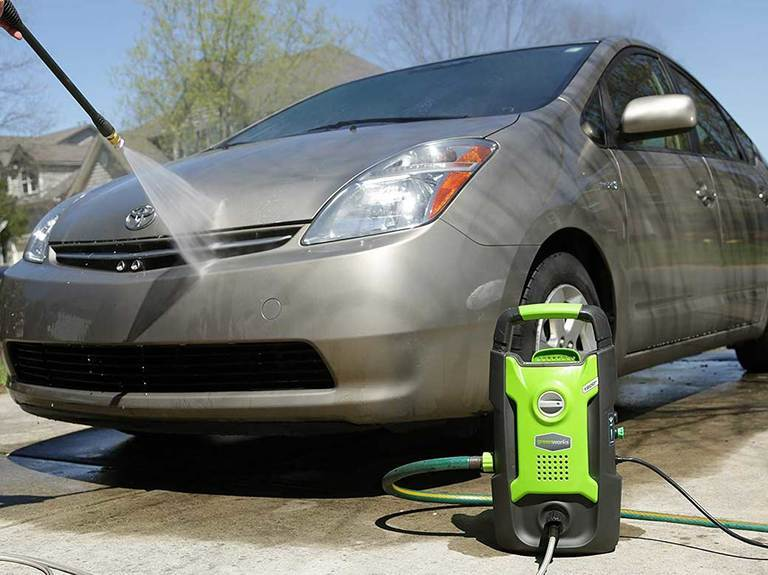 Greenworks pressure washer cleaning a car.